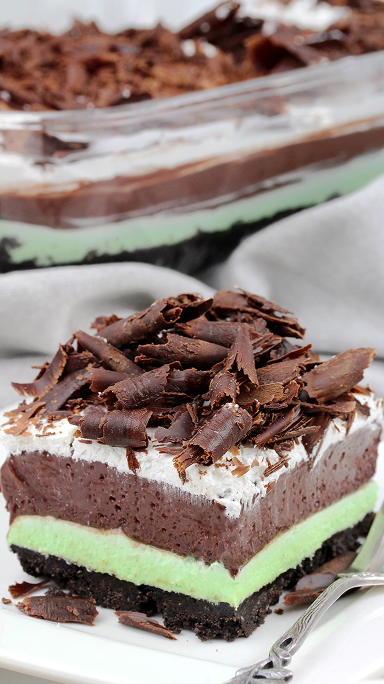 Mint Chocolate Lasagna easy no-bake dessert with layers of Oreo crust, Mint cream cheese, Chocolate pudding, Whipping Cream and Chocolate Curls on top.
