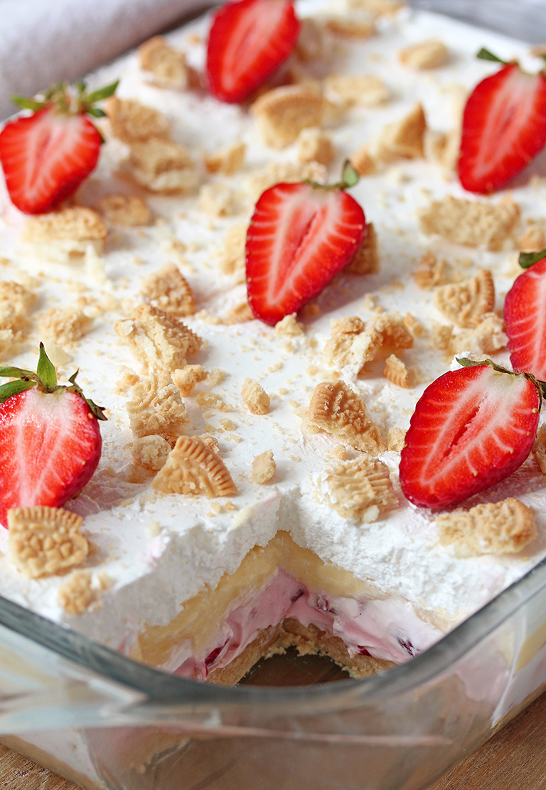 No Bake Strawberry Lush is a layered dessert with golden Oreo crust and creamy layers of strawberry cheesecake and vanilla pudding, topped with whipped cream, crushed golden Oreos and strawberries.