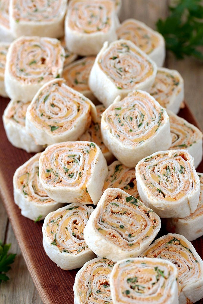 Taco Tortilla Roll Ups this quick and easy party appetizer filled with cream cheese, sour cream, chicken, cheddar cheese, taco seasoning, taco sauce and parsley is perfect for every holiday or a party.