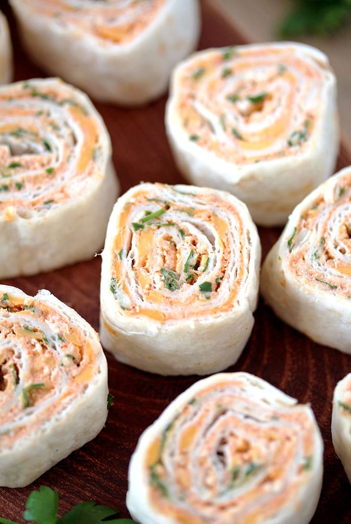 Taco Tortilla Roll Ups – this quick and easy party appetizer filled with cream cheese, sour cream, chicken, cheddar cheese, taco seasoning, taco sauce and parsley is perfect for every holiday or a party