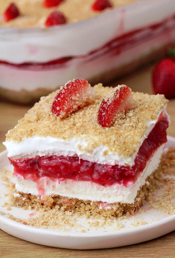 Strawberry Yum Yum – this quick and easy recipe, for no bake, layered dessert will surely become one of your favorites. What makes this cake truly delicious is graham cracker layer, followed by cheesecake, and then strawberry layer, another cheesecake and all is topped with graham cracker crumbs
